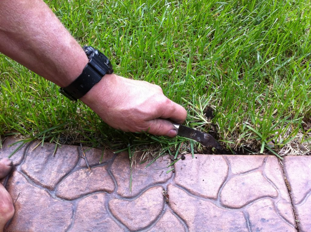 Use a hooked knife for edging the grass back a bit from the curb