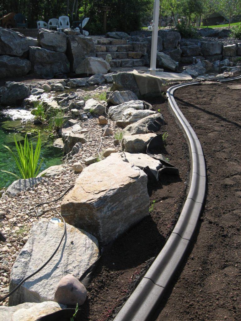 prevent grass migration into pond area